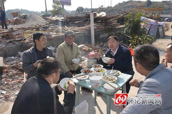 2015年12月,蒙汉在屈原大道项目建设工地与搬迁群众一起吃饭(资料图片)